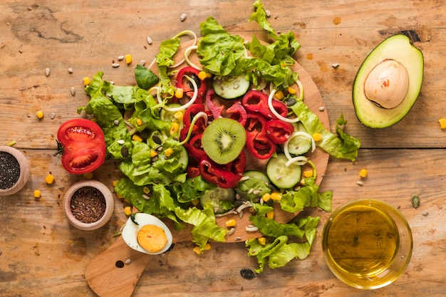 Legumes picados e frutas na tábua com ingredientes; ovo cozido e óleo no pano de fundo de madeira