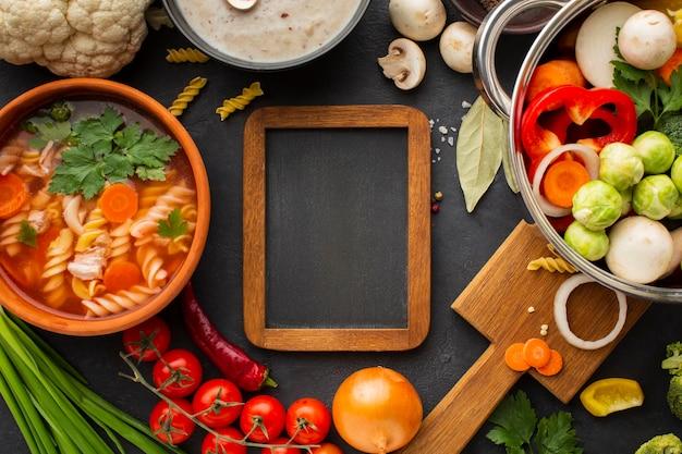 Legumes plana leigos na panela com sopa de legumes com fusilli e moldura de madeira