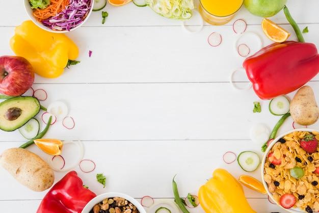 Legumes; salada; tigela de frutas e sucrilhos na mesa de madeira branca com espaço para escrever o texto