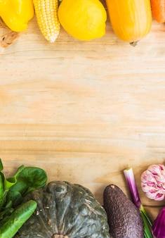 Legumes saudáveis frescos em fundo de madeira
