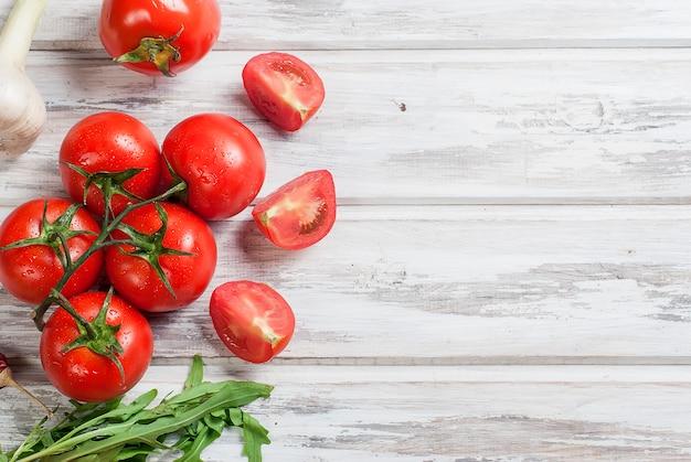 Legumes sazonais, tomate cereja em um galho, folhas de rúcula.