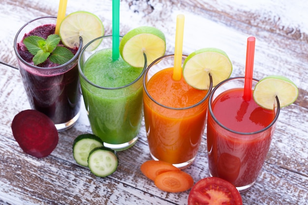 Legumes, sucos frescos misturam bebidas saudáveis de frutas na mesa de madeira.