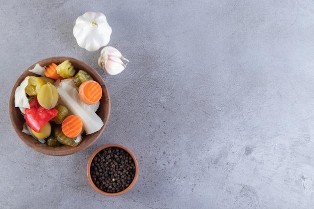 Legumes variados de pickles colocados sobre um fundo de pedra.