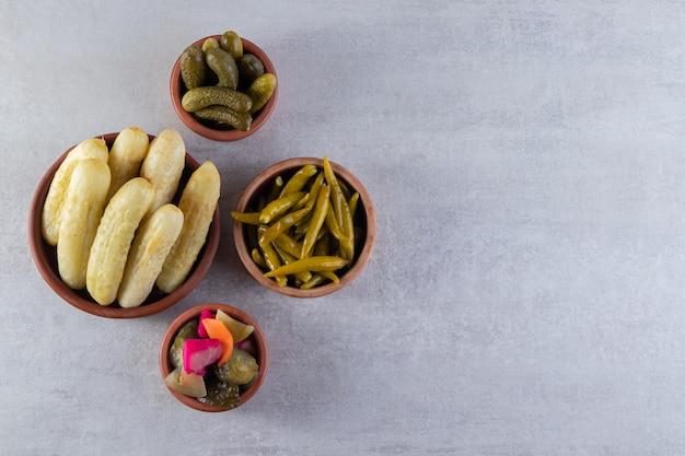 Legumes variados em pickles colocados sobre uma superfície de pedra.