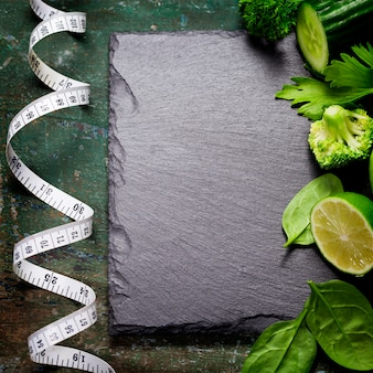 Legumes verdes frescos e fita métrica