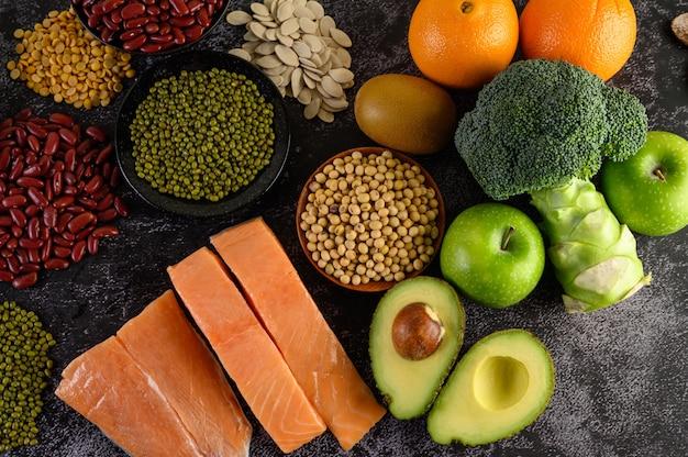 Leguminosas, brócolis, frutas e salmão colocados sobre um piso de cimento preto.