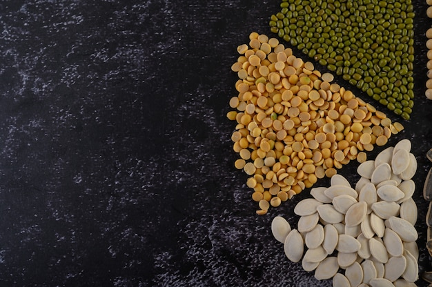 Leguminosas dispostas em círculo no chão de cimento preto.