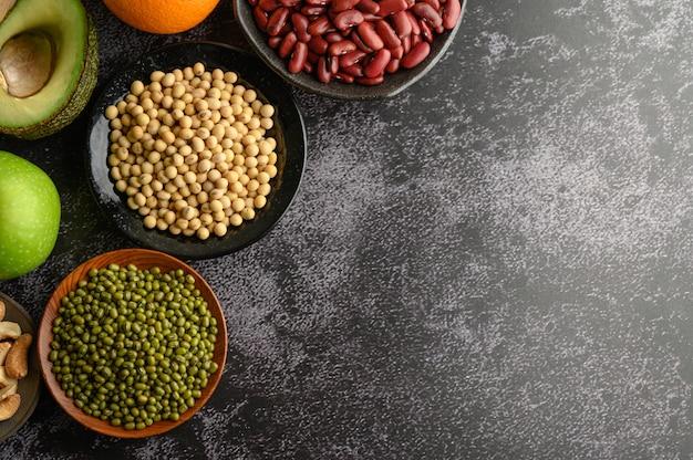 Leguminosas e frutas em pisos de cimento preto.