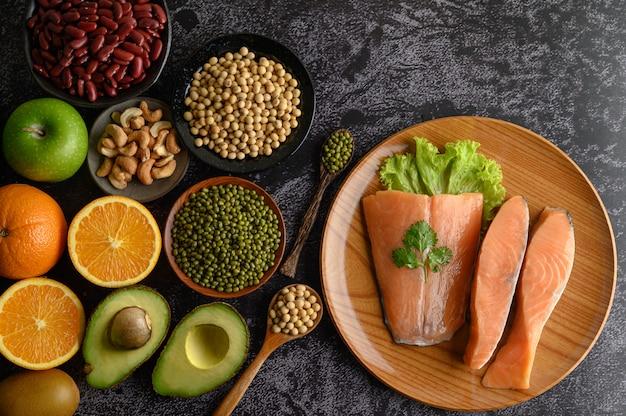 Leguminosas, frutas e pedaços de salmão em uma placa de madeira.