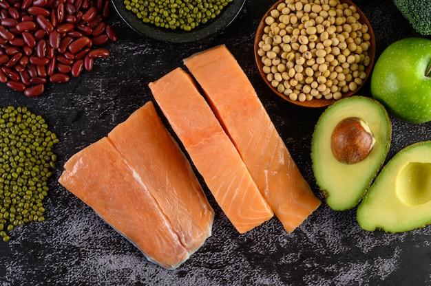Leguminosas, frutas e salmão colocados sobre um piso de cimento preto.