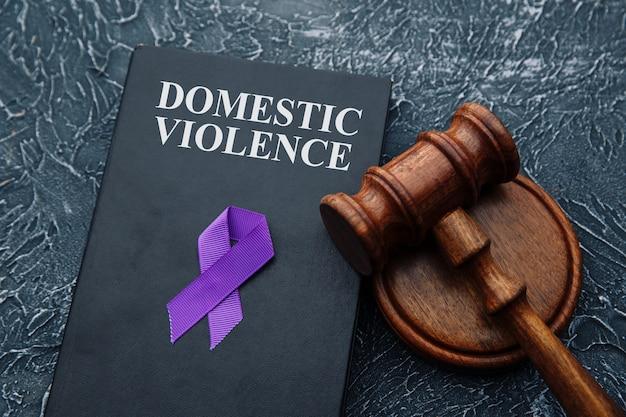 Lei da violência doméstica e martelo na mesa cinza.