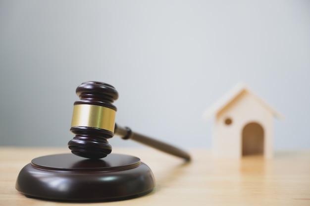 Lei e justiça, conceito de legalidade, martelo de juiz e casa na mesa de madeira