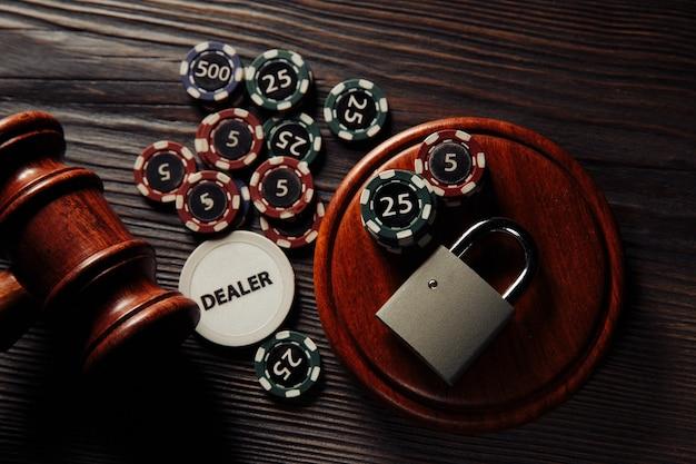 Lei e regras para o conceito de jogos de azar online, martelo de juiz e cadeado com cartas e fichas em close-up de mesa de madeira