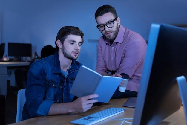 Leia isso. homem atraente, legal e inteligente sentado à mesa e mostrando um livro para seu colega enquanto trabalhava no projeto