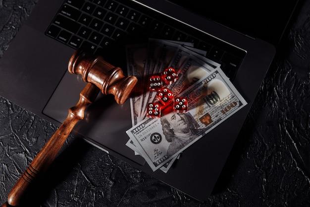 Leis e regras para jogos de azar online, martelo de juiz e dados no teclado.