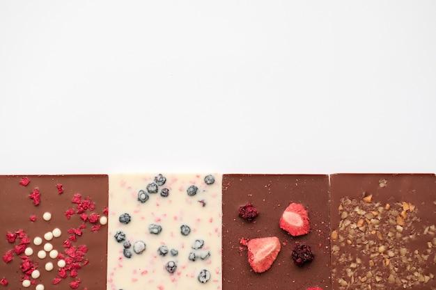 Leite artesanal e barras de chocolate branco com uma variedade de frutas secas