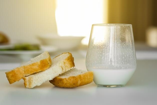 Leite azedo de iogurte ou kefir em um copo de vidro sobre uma mesa branca com pão branco.