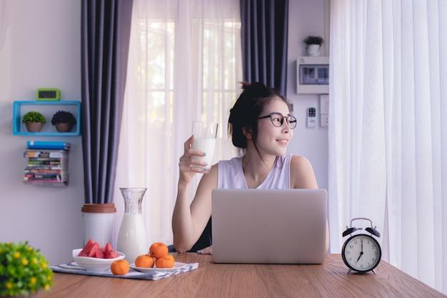 Leite bebendo da mulher asiática nova, tabela de cozinha, estilo de vida asiático novo.