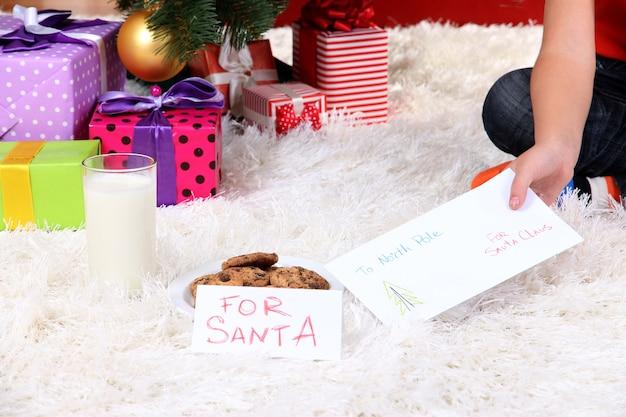 Leite, biscoitos e carta para o papai noel sob a árvore de natal