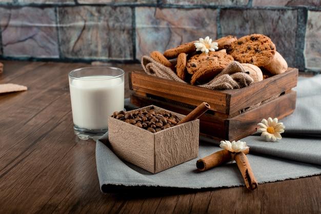 Leite, caixa de café e biscoitos em cima da mesa