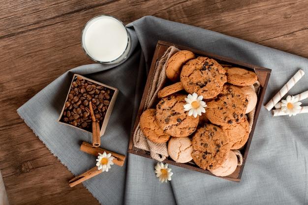 Leite, caixa de café e biscoitos na mesa. vista do topo