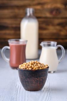 Leite com chocolate e leite de soja em vidro na mesa branca sobre fundo escuro de madeira
