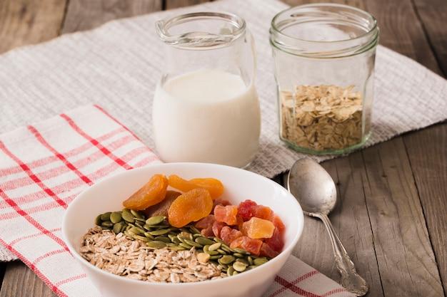 Leite com flocos de aveia, sementes de abóbora e frutas secas na tigela na mesa de madeira