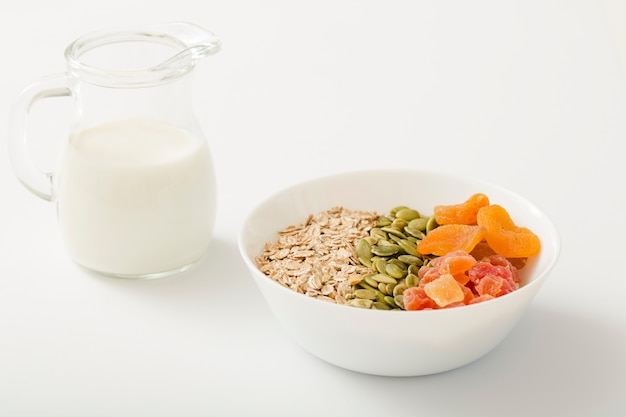 Leite com saudável tigela de cereais, sementes de abóbora e frutas secas na tigela branca sobre fundo branco
