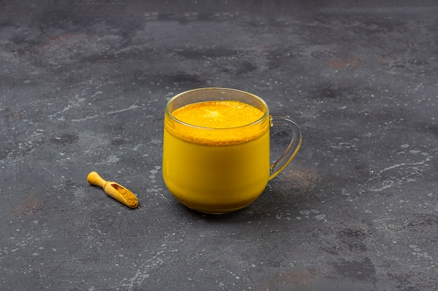 Leite de açafrão indiano tradicional em caneca de vidro com colher de pau