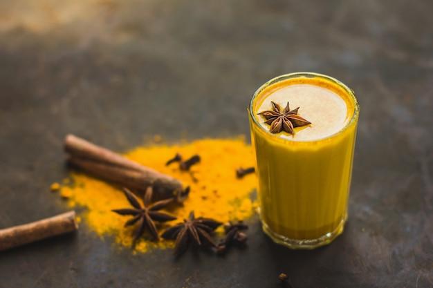 Leite de amêndoa dourada ou café com leite de cúrcuma de abóbora com açafrão em pó em um close-up de fundo escuro. bebida desintoxicante natural asiática moderna com especiarias para veganos