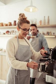 Leite de aquecimento. barista sorridente de óculos em pé ao lado da máquina de café e espumando leite para o cappuccino.