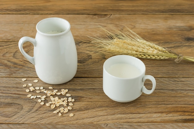 Leite de aveia em uma jarra de vidro e farinha de aveia em um copo sobre uma mesa de madeira.