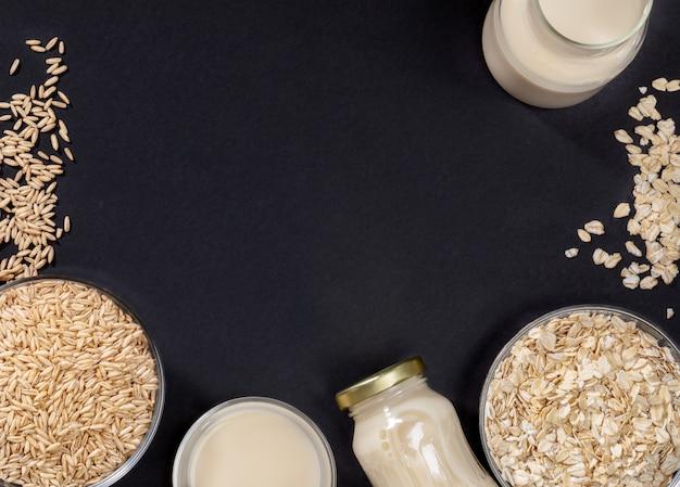 Leite de aveia saudável em garrafas de vidro e sementes de aveia em taças de vidro