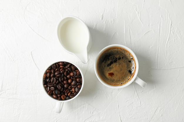 Leite de café fresco e grãos de café sobre fundo branco