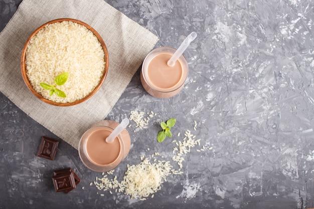 Leite de chocolate de arroz não lácteos orgânicos em vidro e placa de madeira