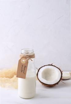 Leite de coco fresco em frasco de vidro com metade do coco fresco em rústico de madeira branco
