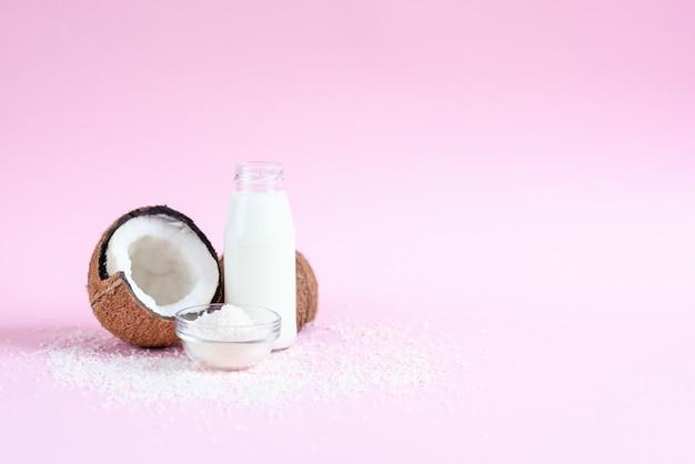 Leite de coco na garrafa de vidro, flocos de coco e coco fresco em fundo rosa.