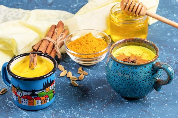 Leite de cúrcuma dourado em dois copos azuis e ingredientes para cozinhar em guardanapo amarelo. pano de fundo azul. foco seletivo.