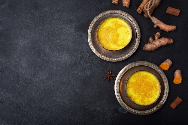Leite de cúrcuma dourado na mesa preta com ingredientes