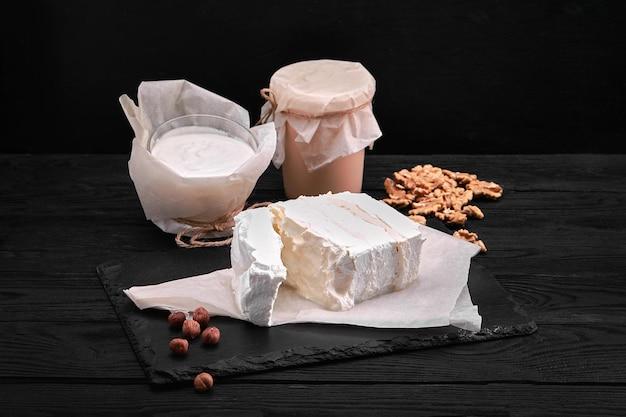 Leite de laticínios diversos, iogurte, queijo cottage, creme de leite. ainda vida rústica. produtos lácteos da vaca do fazendeiro.