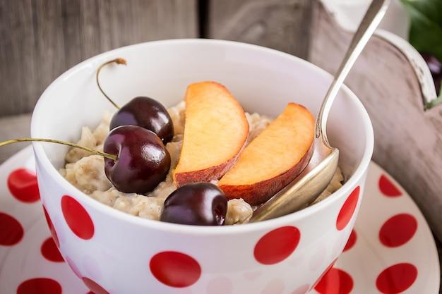 Leite de mingau de aveia com frutas: pêssegos e cerejas. café da manhã saudável