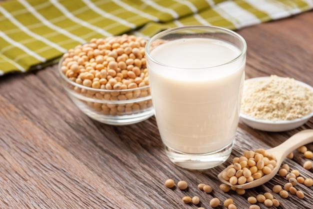 Leite de soja caseiro e feijão de soja com farinha de soja no fundo de madeira, bebida saudável.