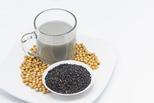 Leite de soja com gergelim preto em vidro no fundo branco.