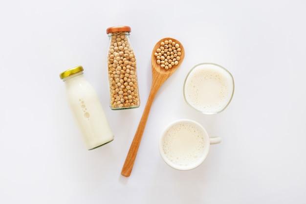 Leite de soja e feijão de soja no fundo branco.