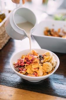 Leite de soja servindo em uma tigela com manga fresca, abacate, banana, frutas vermelhas, sementes, sementes de chia, cereais