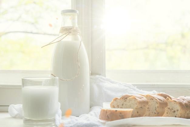 Leite de vaca cru fresco no parapeito de uma janela, café da manhã saudável na aldeia, despeje o leite em um copo