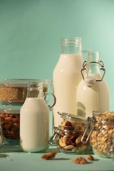 Leite de vaca substituto vegan. garrafas de vidro com leite e ingredientes da não-leiteria sobre o fundo azul com espaço da cópia.