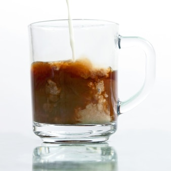 Leite derramado em uma xícara transparente de café preto. bebida quente favorita