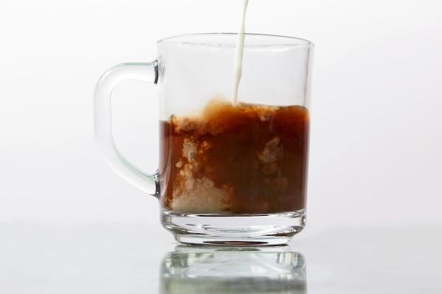 Leite derramado em uma xícara transparente de café preto