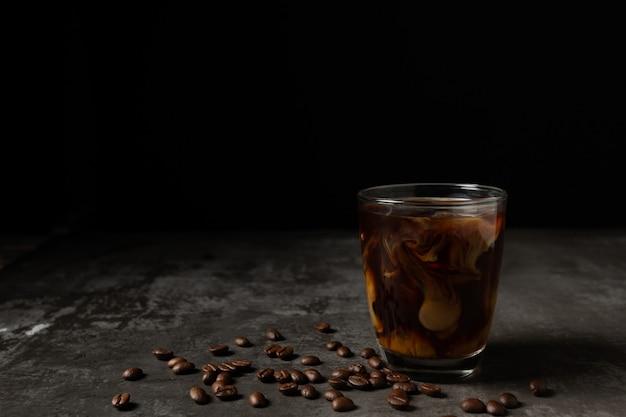 Leite, derramando em café preto gelado na mesa